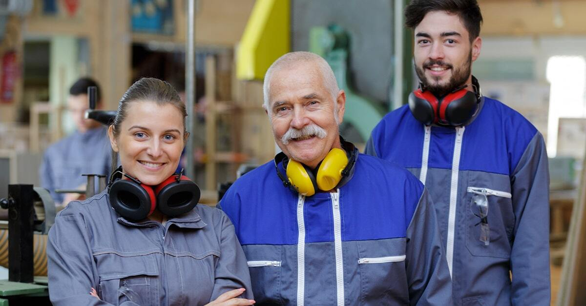 Reynolds-Training-Apprenticeships-two-young-apprentices-smiling-one-older-trainer-also-smiling